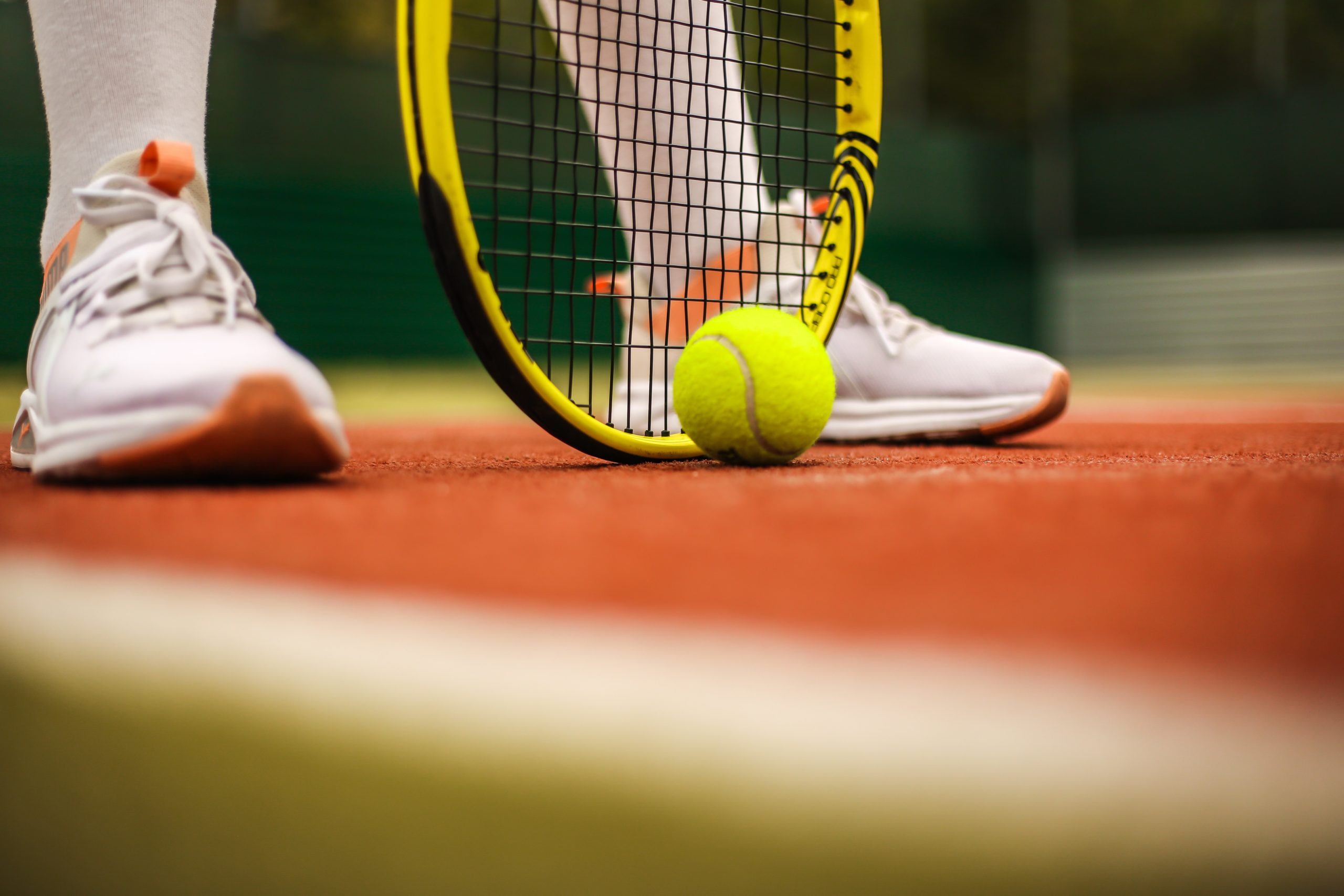 Tennis shoes, racket and ball