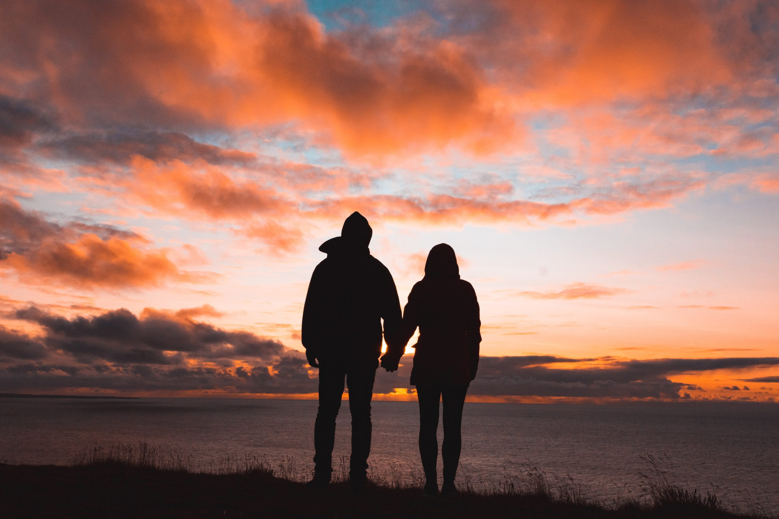 couple standing together, holding hands, looking out over the hill